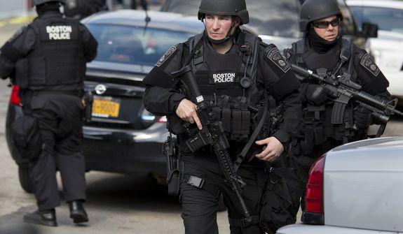 Heavily armed police continue to patrol the neighborhoods of Watertown, Mass. Friday, April 19, 2013, as they continue a massive search for one of two suspects in the Boston Marathon bombing. A second suspect died in the early morning hours after an encounter with law enforcement. (AP Photo/Craig Ruttle)