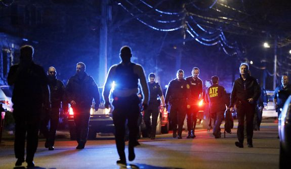Police officers walk near a crime scene Friday, April 19, 2013, in Watertown, Mass. A tense night of police activity that left a university officer dead on campus just days after the Boston Marathon bombings and amid a hunt for two suspects caused officers to converge on a neighborhood outside Boston, where residents heard gunfire and explosions. (AP Photo/Matt Rourke)