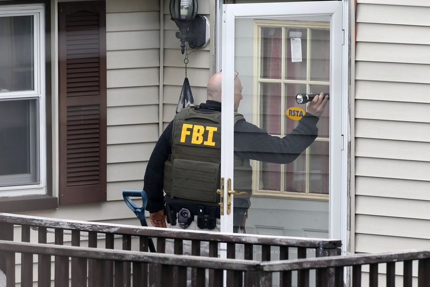 An FBI agent goes door-to-door evacuating residents of Norfolk Street as investigators search for a suspect in the Boston Marathon bombings, in Cambridge, Mass., Friday, April 19, 2013. Two suspects in the Boston Marathon bombing killed an MIT police officer, injured a transit officer in a firefight and threw explosive devices at police during a getaway attempt in a long night of violence that left one of them dead and another still at large Friday, authorities said as the manhunt intensified for a young man described as a dangerous terrorist.(AP Photo/Michael Dwyer)