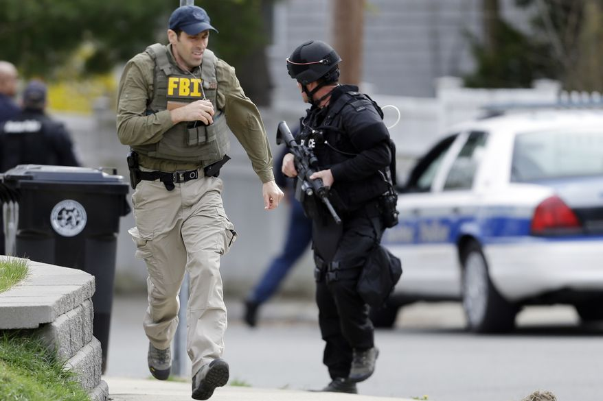 A police officer and a Federal Bureau of Investigation agent run as they conduct a search for a suspect in the Boston Marathon bombings, Friday, April 19, 2013, in Watertown, Mass. The two suspects in the Boston Marathon bombing killed an MIT police officer and hurled explosives at police in a car chase and gun battle overnight that left one of them dead and his brother on the loose, authorities said Friday as thousands of officers swarmed the streets in a manhunt that all but paralyzed the Boston area. (AP Photo/Matt Rourke)