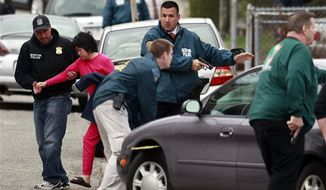 ** FILE ** A neighbor is escorted to safety as police surround a home while searching for a suspect in the Boston Marathon bombings in Watertown, Mass., Friday, April 19, 2013. (AP Photo/Charles Krupa)
