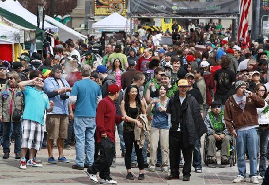 Crowds begin to gather at the Denver 4/20 pro-marijuana rally at Civic Center Park in Denver on Saturday, April 20, 2013. Authorities generally look the other way at public pot smoking here on April 20. (AP Photo/Brennan Linsley)