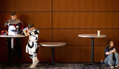 "Justin Youtz of Woodbridge, Va., dressed as Anakin Skywalker reads comics with his son Tristin, 9, dressed as Captain Rex from Star Wars at Awesome Con D.C. Will Makaneole of Dumfries, Va., wears a wookie-like jacket from the ""Star Wars"" movies as he takes pictures during the costume contest."