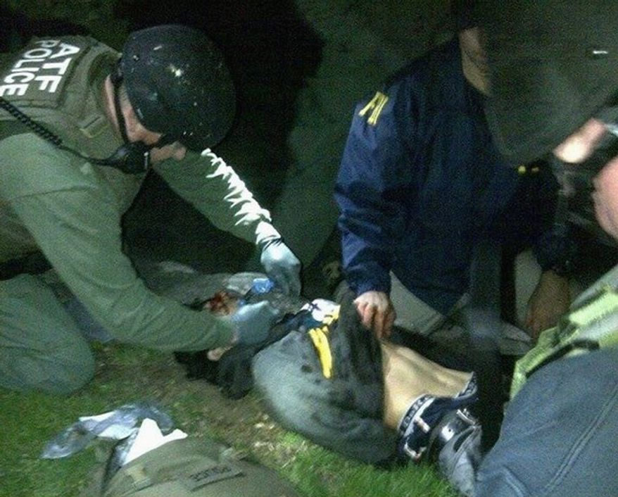 ** FILE ** Agents of the FBI and Bureau of Alcohol, Tobacco, Firearms and Explosives check suspect Dzhokhar Tsarnaev for explosives and give him medical attention after his capture in Watertown,