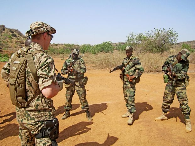A Swedish instructor watches as Malian soldiers practice arming their weapons in the village of Koulikoro, outside Bamako, Mali. In preparation for the final pullout of French troops from Mali, a European Union team has started training Malian soldiers to battle jihadists. (Associated Press)