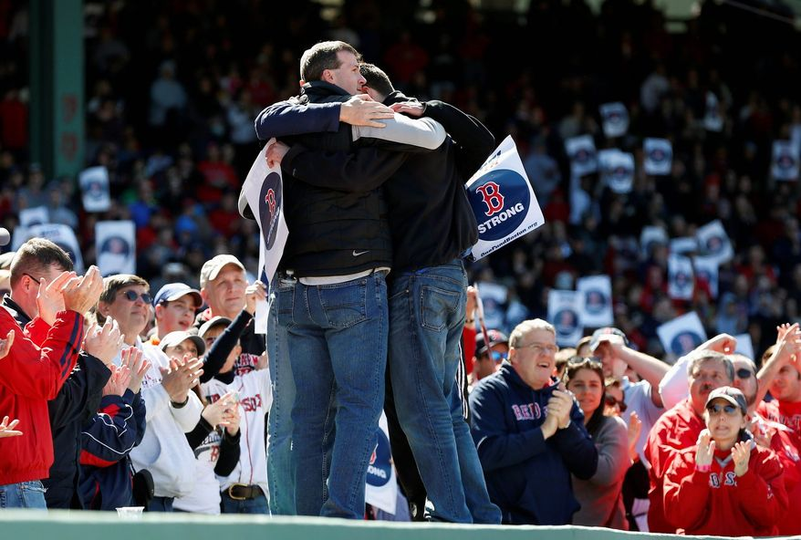 Sticking together: A group of first responders to the Boston Marathon bombings comfort one another during a tribute during a baseball doubleheader between the Boston Red Sox and the Kansas City Royals on Sunday.