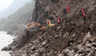 Chinese paramilitary policemen stand watch on Sunday, April 21, 2013, while rescuers operate backhoes to clear a road damaged by a landslide that was triggered by a strong earthquake in Baosheng township of Lushan County in southwest China's Sichuan province. Saturday's earthquake in Sichuan province killed more than 186 people, China's Xinhua News Agency said. (AP Photo)