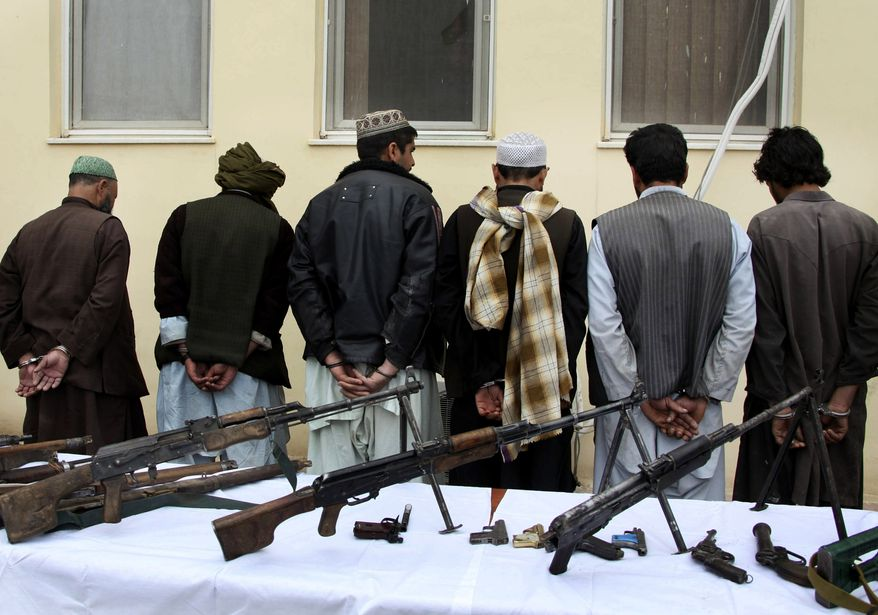 ** FILE ** Former Taliban members, handcuffed, stand in line after turning in their weapons during a ceremony with the Afghan government in Herat, Afghanistan, on Sunday, April 7, 2013, as part of a peace-reconciliation program. (AP Photo/Hoshang Hashimi)