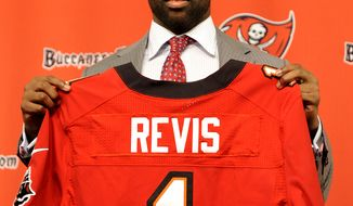 NFL football cornerback Darrelle Revis holds up a Tampa Bay Buccaneers jersey after addressing the media announcing that he and the Buccaneers have agreed on a six-year contract during a press conference Monday, April, 22, 2013, in Tampa, Fla. The Buccaneers acquired Revis from the New York Jets in exchange for their first-round pick in the 2013 NFL Draft and a conditional selection in the 2014 NFL Draft. (AP Photo/Brian Blanco)
