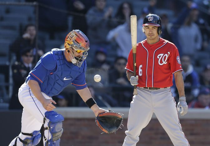 New York Mets catcher John Buck, left, tosses the ball up after the Nationals Anthony Rendon, right, struck out looking for the final out of the Mets' 2-0 shutout of the Nationals in a baseball game at Citi Field in New York, Sunday, April 21, 2013. (AP Photo/Kathy Willens)
