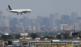** FILE ** A United Airlines jetliner prepares to land at Newark Liberty International Airport in Newark, N.J., on July 10, 2012. The New York City skyline is in the background. (AP Photo/Julio Cortez)