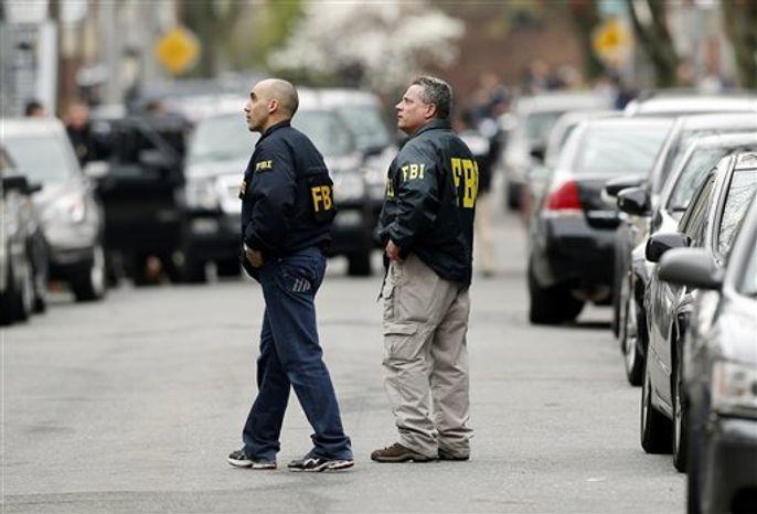** FILE ** FBI agents walk along Norfolk Street in Cambridge, Mass., on April 19, 2013. (Associated Press)