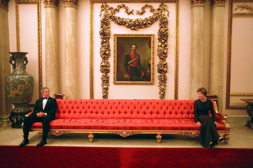 President George W. Bush and Mrs. Laura Bush sit on either ends of a couch prior to a social event at Buckingham Palace.  Photographs by Eric Draper from Front Row Seat: A Photographic Portrait of the Presidency of George W. Bush(Copyright © 2013). For more information visit www.utexaspress.com