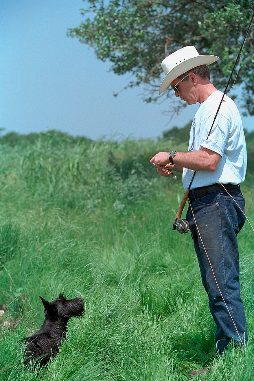 Barney waits for a treat as his master works on the line during a fishing outing Sunday, April 28, 2002, at the pond on Prairie Chapel Ranch in Crawford, Texas.  Photographs by Eric Draper from Front Row Seat: A Photographic Portrait of the Presidency of George W. Bush(Copyright © 2013). For more information visit www.utexaspress.com