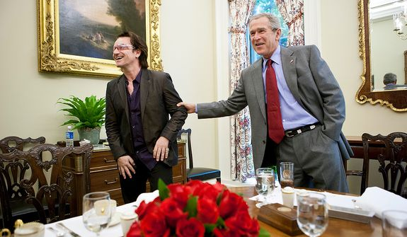 President george W. Bush goofs with Bono during lunch Wednesday, Oct. 19, 2005, in the Private Oval Office Dining Room of the White House.  Photographs by Eric Draper from Front Row Seat: A Photographic Portrait of the Presidency of George W. Bush(Copyright © 2013). For more information visit www.utexaspress.com