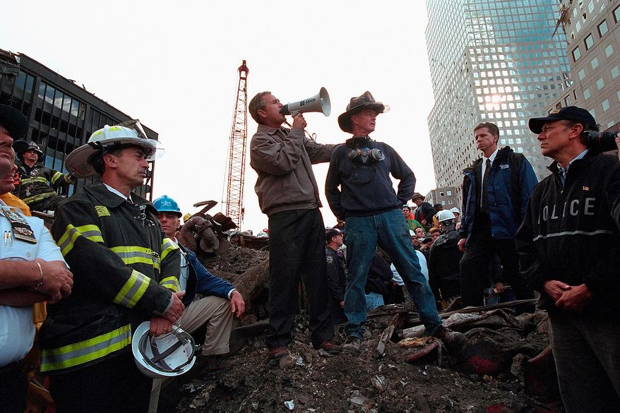 "Standing on top of a crumpled fire truck with retired New York City firefighter Bob Beckwith, President George W. Bush rallies firefighters and rescue workers Friday, Sept. 14, 2001, during an impromptu speech at the site of the collapsed World Trade Center towers in New York City. ""I can hear you,"" President Bush said. ""The rest of the world hears you. And the people who knocked these buildings down will hear all of us soon.""  Photographs by Eric Draper from Front Row Seat: A Photographic Portrait of the Presidency of George W. Bush(Copyright © 2013). For more information visit www.utexaspress.com"