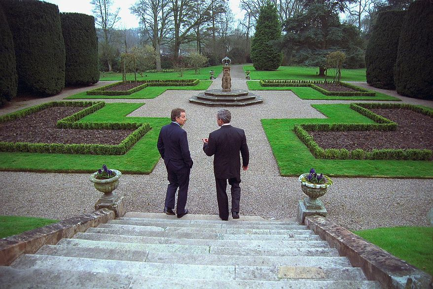 President George W. Bush and Prime Minister Tony Blair of Great Britain walk on the grounds of Hillsborough Castle Monday, April 7, 2003, in Hillsborough, Northern Ireland. Photographs by Eric Draper from Front Row Seat: A Photographic Portrait of the Presidency of George W. Bush(Copyright © 2013). For more information visit www.utexaspress.com