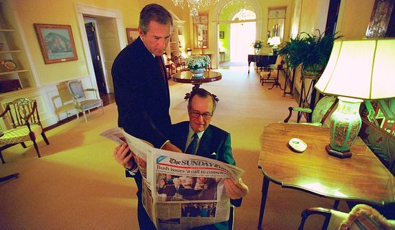 As President George W. Bush reads over his shoulder, former President George H.W. Bush reads the Sunday Times Sunday, Jan. 21, 2001, in the Private Residence of the White House.   Photographs by Eric Draper from Front Row Seat: A Photographic Portrait of the Presidency of George W. Bush(Copyright © 2013). For more information visit www.utexaspress.com