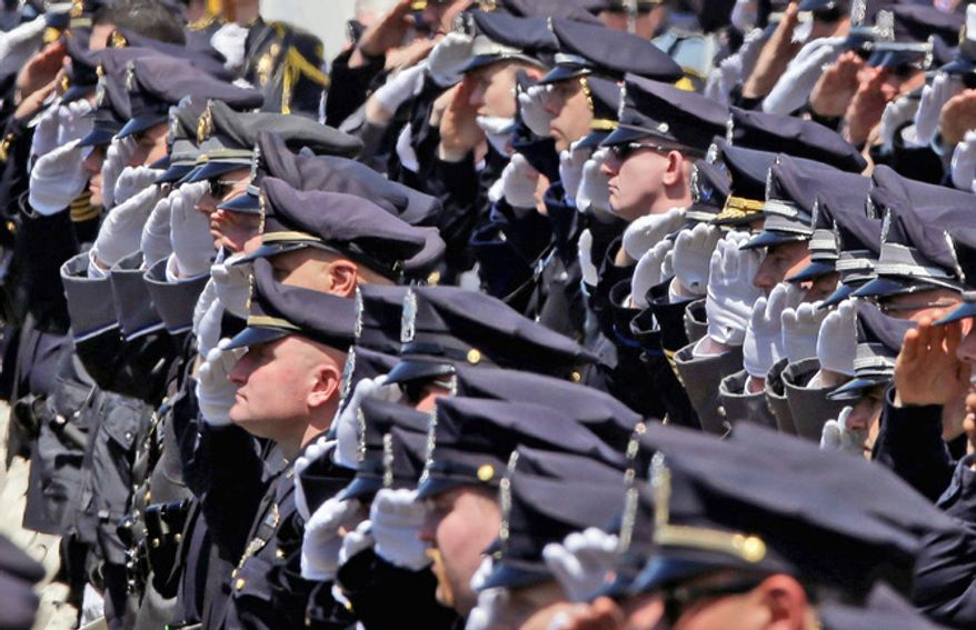 ** FILE ** Police officers salute during a memorial service for fallen Massachusetts Institute of Technology campus officer Sean Collier at MIT in Cambridge, Mass. Wednesday, April 24, 2013. Sean Collier was fatally shot on the MIT campus Thursday, April 18, 2013. Authorities allege that the Boston Marathon bombing suspects were responsible. (AP Photo/Elise Amendola)
