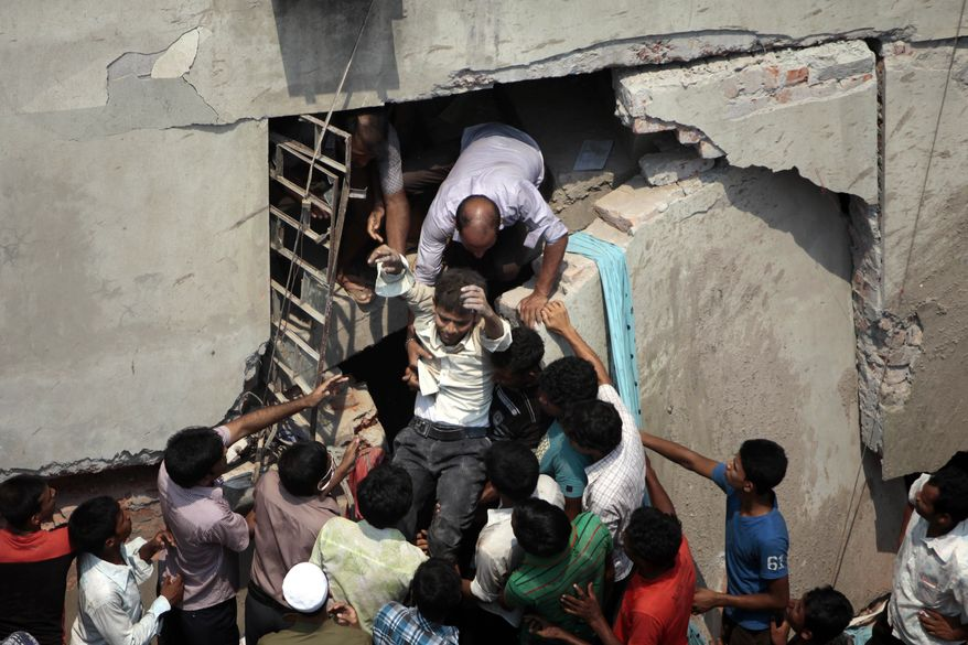 A man who was trapped in an eight-story building housing several garment factories is rescued after the structure collapsed in Savar, near Dhaka, Bangladesh, Wednesday, April 24, 2013. The building collapsed near Bangladesh's capital Wednesday morning, killing dozens of people and trapping many more in the rubble, officials said. (AP Photo/ A.M. Ahad)