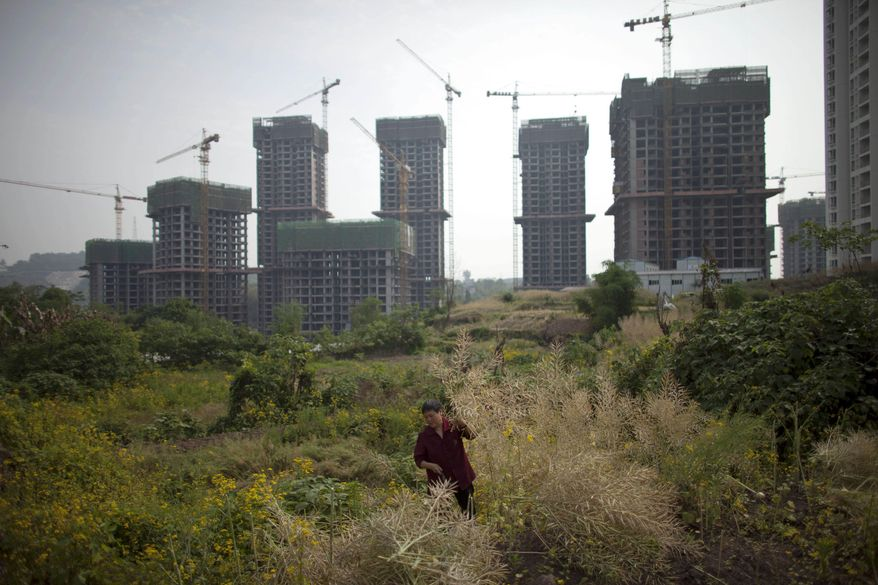 A woman cuts weeds in a field near an unfinished real estate project in Chongqing, China, Tuesday, April 23, 2013. (AP Photo/Alexander F. Yuan)