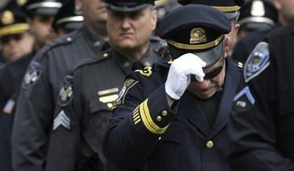 A Revere, Mass. police captain holds his cap while entering a memorial service for fallen Massachusetts Institute of Technology police officer Sean Collier, in Cambridge, Mass., Wednesday, April 24, 2013. Collier was fatally shot on the MIT campus Thursday, April 18, 2013. Authorities allege that the Boston Marathon bombing suspects were responsible. (AP Photo/Steven Senne)