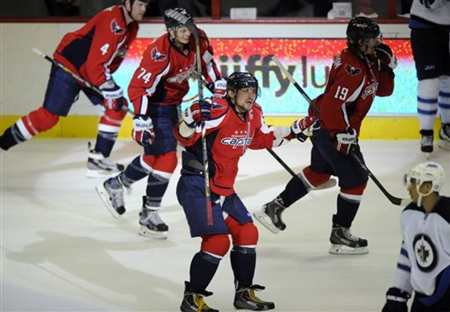 Washington Capitals left wing Alex Ovechkin (8), of Russia, gestures after he scored and an empty-net goal against the Winnipeg Jets during the third period of an NHL hockey game, Tuesday, April 23, 2013, in Washington. The Capitals won 5-3. Capitals defenseman John Carlson (74), John Erskine (4) and Nicklas Backstrom (19), of Sweden, and Jets left wing Evander Kane skate around Ovechkin. (AP Photo/Nick Wass)