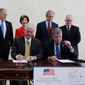 Bush Center president Mark Langdale, front left and national archivist David Ferriero, right, sign a joint use agreement for the George W. Bush Presidential Center Wednesday, April 24, 2013, in Dallas. At rear from left are board chairman of the George W. Bush Foundation Don Evans, former first lady Laura Bush, former president George W. Bush, and Bush Center Director Alan Lowe. (AP Photo/David J. Phillip)