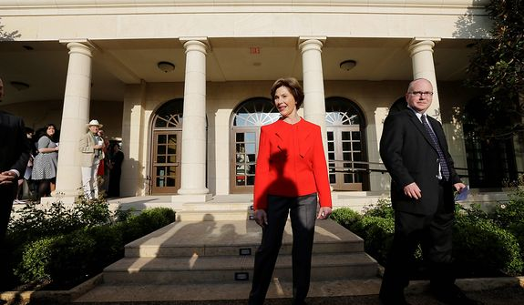 Former first lady Laura Bush and Alan Lowe, director of the library and museum enter a replica of the White House rose garden during a tour of the George W. Bush Presidential Center Wednesday, April 24, 2013, in Dallas.  More than 8,000 people are expected to attend the invitation-only dedication of the center, Thursday, April 25, which will house the presidential library and museum along with the 43rd presidentís policy institute. It opens to the public on May 1.  (AP Photo/David J. Phillip)