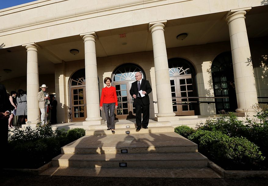 Former first lady Laura Bush and Alan Lowe, director of the library and museum enter a replica of the White House rose garden during a tour of the George W. Bush Presidential Center Wednesday, April 24, 2013, in Dallas. (AP Photo/David J. Phillip)