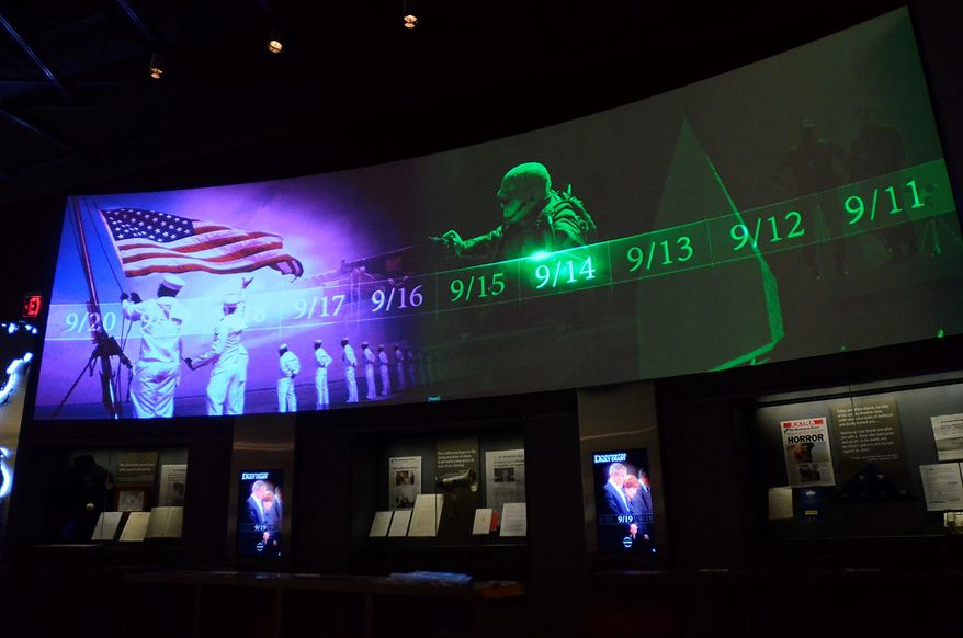 In this photo taken April 16, 2013, a large screen displays images and video of the events and days that followed the 9/11 terrorist attacks as part of an exhibit in the museum area at the George W. Bush Presidential Library and Museum in Dallas.  The museum uses everything from news clips to interactive screens to artifacts to tell the story of Bushís eight years in office. The George W. Bush Presidential Center, which includes the library and museum along with 43rd presidentís policy institute, will be dedicated Thursday on the campus of Southern Methodist University in Dallas. (AP Photo/Benny Snyder)