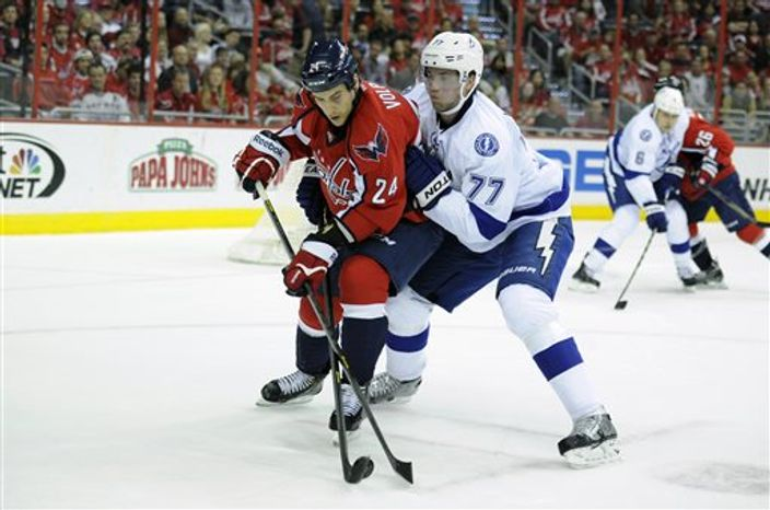 Tampa Bay Lightning defenseman Victor Hedman (77), of Sweden, battles for the puck against Washington Capitals left wing Aaron Volpatti (24) during the first period of an NHL hockey game, Saturday, April 13, 2013, in Washington. (AP Photo/Nick Wass)