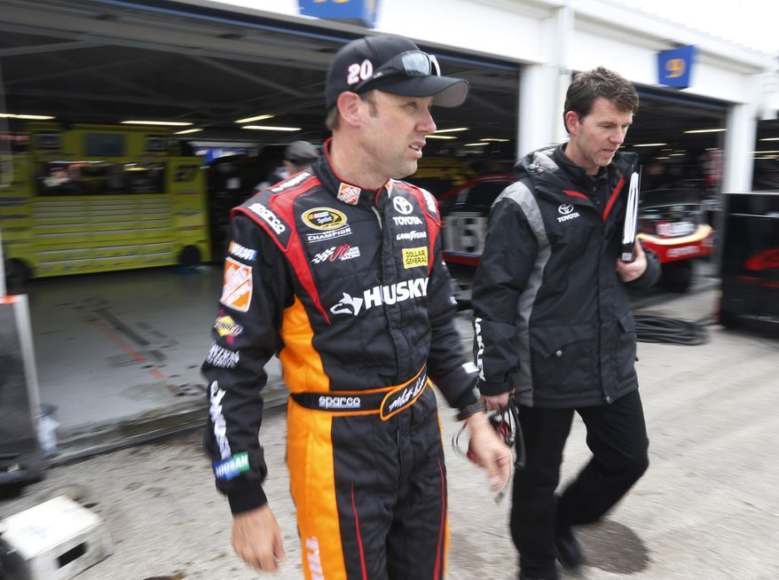 FILE - In this April 20, 2013 file photo, Matt Kenseth, left, walks from the garage following practice for the NASCAR Sprint Cup series STP 400 auto race at Kansas Speedway in Kansas City, Kan. Kenseth's race-winning car from Kansas failed inspection at NASCAR's Research and Development Center, The Associated Press has learned. NASCAR officials were discussing Wednesday, April 24, 2013 what penalties to levy against Kenseth and Joe Gibbs Racing, multiple people familiar with the inspection told the AP on the condition of anonymity because no decision has been made. (AP Photo/Orlin Wagner, File)