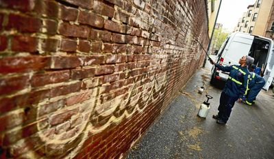 Denita Taylor of the District's six-person graffiti cleanup crew sprays chemicals to remove spray paint in an alley near 14th and U streets Northwest on Thursday. (Andrew Harnik/The Washington Times)