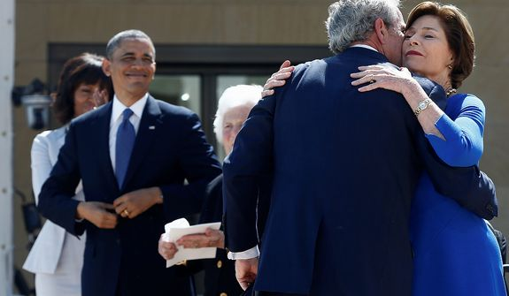 President Barack Obama, first lady Michelle Obama and former first lady Barbara Bush watch as former President George W. Bush hugs his wife, former first lady Laura Bush at the dedication of the George W. Bush presidential library on the campus of Southern Methodist University in Dallas, Thursday, April 25, 2013. (AP Photo/Charles Dharapak)