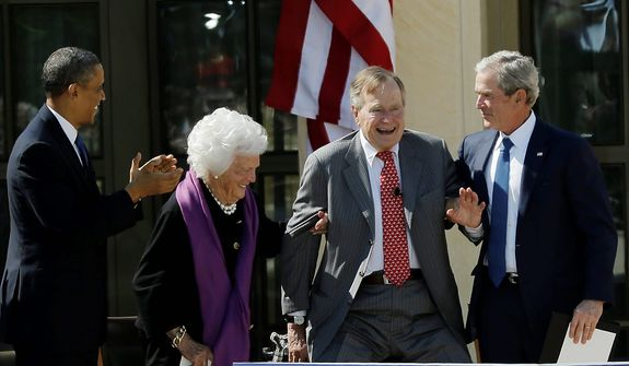 As President Obama (left) applauds, former first lady Barbara Bush (second from left) and former President George W. Bush (right) help former President George H.W. Bush stand to acknowledge a standing ovation during the dedication of the George W. Bush Presidential Center on Thursday, April 25, 2013, in Dallas. (AP Photo/David J. Phillip)