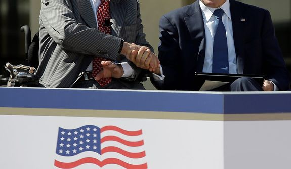 Former President George H.W. Bush shakes hands with his son, former President George W. Bush during the dedication of the George W. Bush Presidential Center, Thursday, April 25, 2013, in Dallas. (AP Photo/David J. Phillip)
