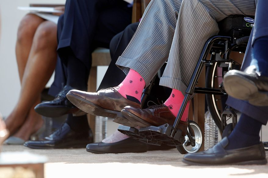Former President George H.W. Bush, wears pink socks as he is seated in a wheelchair with, from left, first lady Michelle Obama, President Barack Obama, former first lady Barbara Bush, and former President George W. Bush, at the dedication of the George W. Bush presidential library on the campus of Southern Methodist University in Dallas, Thursday, April 25, 2013. (AP Photo/Charles Dharapak)