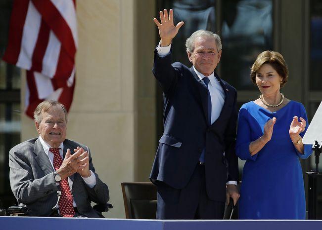 Former president George H.W. Bush, left, applauds with Laura Bush after former president George W. Bush's speech during the dedication of the George W. Bush Presidential Center Thursday, April 25, 2013, in Dallas. (AP Photo/David J. Phillip)