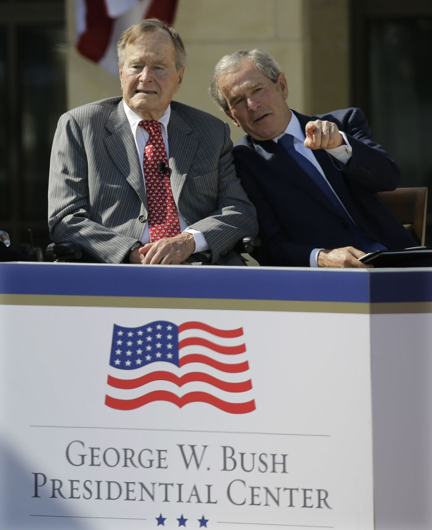Former president George W. Bush, right, speaks with his father former president George H.W. Bush during the dedication of the George W. Bush Presidential Center Thursday, April 25, 2013, in Dallas. (AP Photo/David J. Phillip)
