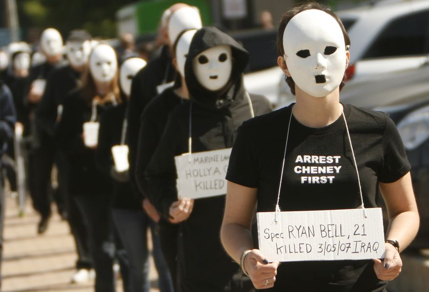 Protesters walk with masks on in Dallas near the dedication of the opening of the George W. Bush Presidential Center in Dallas, on Thursday, April 25, 2013. Police arrested at least three people during the protest march. (AP Photo/Mike Fuentes)