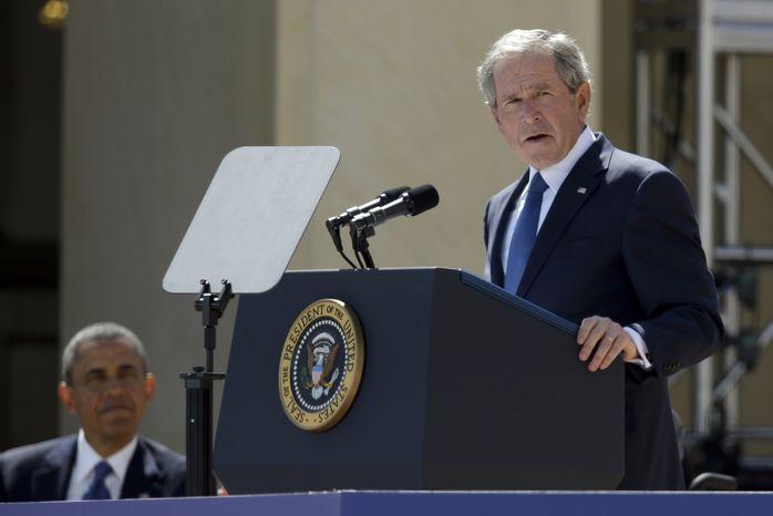 President Barack Obama listens as former President George W. Bush speaks during the dedication of the George W. Bush Presidential Center, Thursday, April 25, 2013, in Dallas. (AP Photo/Tony Gutierrez, Pool)
