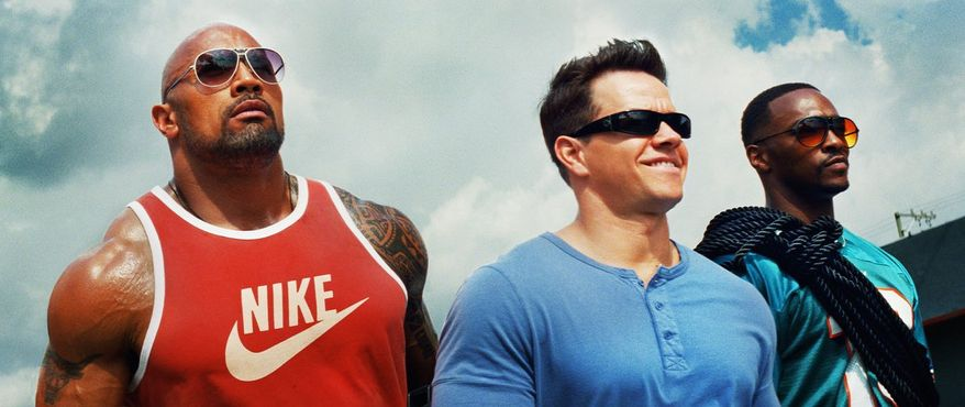 """This undated publicity photo released by courtesy of Paramount Pictures shows, from left, Dwayne Johnson as Paul Doyle, Mark Wahlberg as Daniel Lugo and Anthony Mackie as Adrian Doorbal in the film, """"Pain and Gain,"""" directed by Michael Bay from Paramount Pictures. The film releases in theaters April 26, 2013. (AP Photo/Paramount Pictures)"""