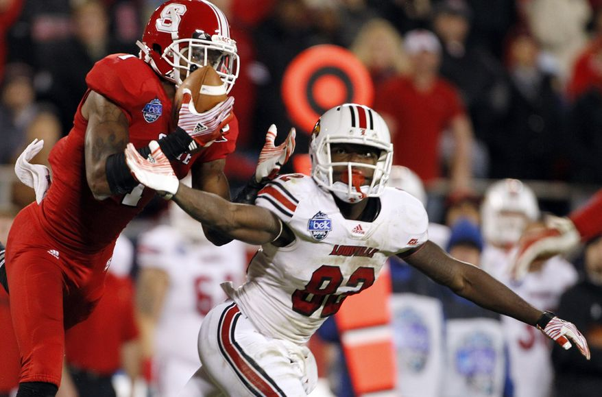 North Carolina State's David Amerson, left, intercepts a pass intended for Louisville's Eli Rogers during the second half of the Belk Bowl NCAA college football game in Charlotte, N.C., Tuesday, Dec. 27, 2011. Amerson returned the interception for a touchdown. (AP Photo/Bob Leverone)