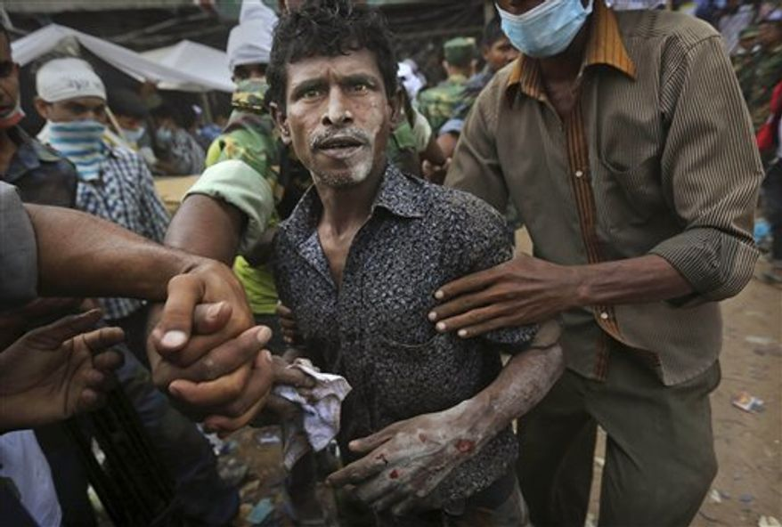 A Bangladeshi garment worker who soldiers said was pulled alive from the rubble reacts as he walk on his own at the site of a building that collapsed Wednesday in Savar, near Dhaka, Bangladesh, Friday, April 26, 2013. By Friday, the death toll reached hundreds of people as rescuers continued to search for injured and missing.(Associated Press)