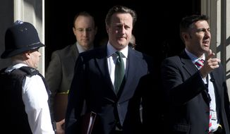 **FILE** Britain Prime Minister David Cameron (center) leaves 10 Downing Street, with unidentified aides, for the House of Commons for the weekly session of Prime Minister's Question Time in the House of Commons in London on April 24, 2013. (Associated Press)
