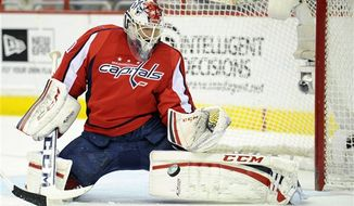 Washington Capitals goalie Braden Holtby (70) tracks the puck against the Tampa Bay Lightning during the second period of an NHL hockey game, Saturday, April 13, 2013, in Washington. (AP Photo/Nick Wass)