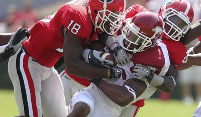 Arkansas wide receiver Greg Childs (85) is stopped by Georgia's Bacarri Rambo (18) and Jakar Hamilton (23) during the first quarter of an NCAA college football game in Athens, Ga., on Saturday, Sept. 18, 2010. (AP Photo/John Bazemore)