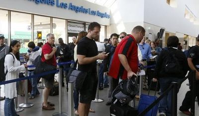 **FILE** Travelers stand in line at the LAX International Airport in Los Angeles on April 22, 2013. (Associated Press)