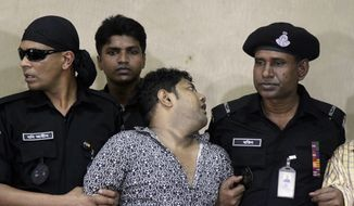Mohammed Sohel Rana (center), the fugitive owner of an illegally constructed building that collapsed last week in Bangladesh, reacts as he is produced before the media in Dhaka, Bangladesh, the capital, on Sunday, April 28, 2013. Mr. Rana was arrested near the border in Benapole, in western Bangladesh, just as he was about to flee into India's West Bengal state, said Jahangir Kabir Nanak, junior minister for local government. (AP Photo/Palash Khan)
